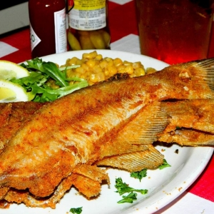 A plate of fried whole catfish with lemons and corn